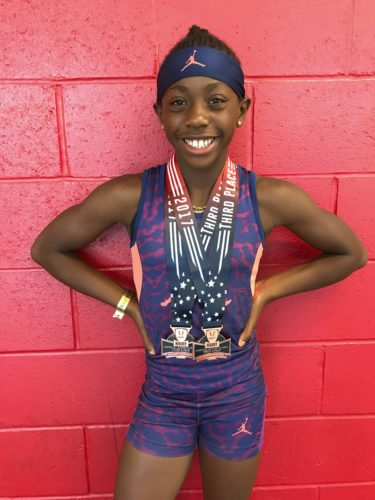Nine-year-old Elecia McCurrie poses with her bronze medals won at this year's U.S.A. Track and Field Junior Olympics. McCurrie, who grew up in Charles Town, placed third in both the 100- and 200-meter dashes this year in the 9-10-year-old division.