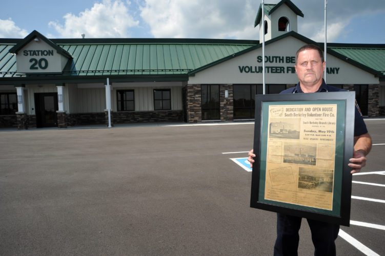 Firefighter Rick Petry holds a framed full page from the Martinsburg Journal from the day the old station was dedicated and placed into service, in front of the newest and largest station in Berkeley County. The new station will be home for South Berkeley Volunteer Fire Department for years to come. (Journal photo by Jeff McCoy)