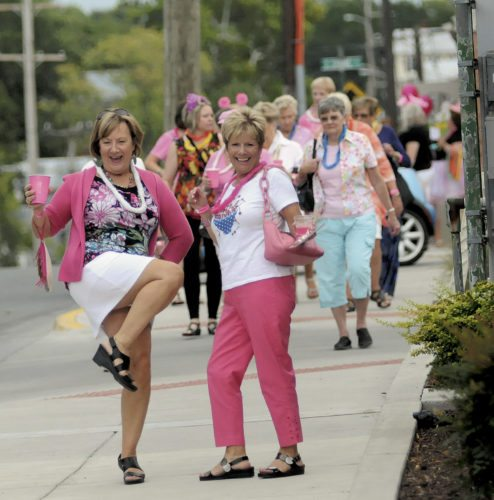 From left: Fundraiser participants Cindy Ferguson and Sheila Joy lead a wave of ladies toward downtown for Flamingo Fandango Girls Night Out. Approximately 200 people ventured through several businesses throughout downtown Martinsburg Friday afternoon.  All donations will directly benefit CASA. (Journal Photo by Ron Agnir)