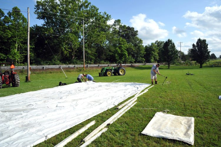Church members repair and prepare to set up a large tent in Back Creek Valley, which will be used for an old-time gospel tent revival.  (Journal photo by Jeff McCoy)