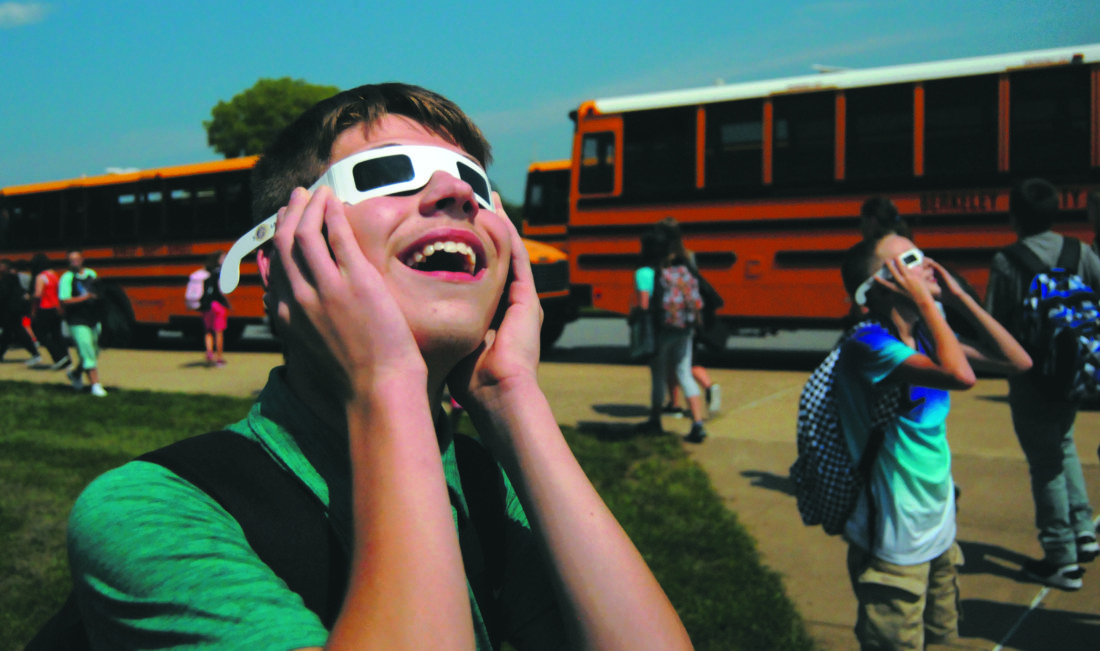 22  Solar Eclipse3 ra 08-21-17 Tyler Kidwell , 7th grade , watches the Solar Eclipse with school supplied glasses just as school lets out at Musselman Middle School in Bunker Hill, WV Tuesday afternoon. (Journal Photo by Ron Agnir)