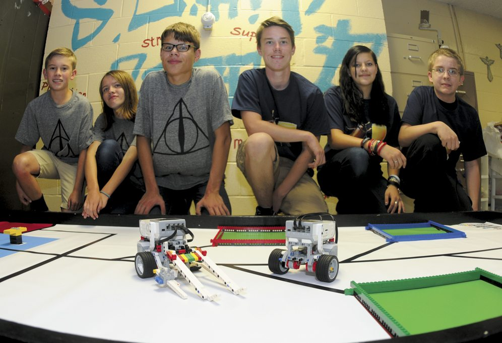 "30 Robotics1 ra 08-29-17 From left: ""Team Deathly Hallows""  Billy McCune, 12; Allsion McCaslin 13; Edward Engle, 14. ""Team Beetle Juice""  Ian Fleming, 15; Emma Engle, 13 and Michael Kaulfuss, 13;  Members of the Berkeley County 4-H STEM Club build and program their robots to navigate through an obstacle course Tuesday evening in Martinsburg. (Journal Photo by Ron Agnir)"