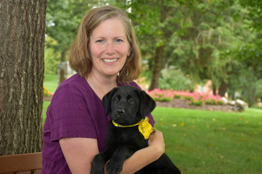 Dr. Amy DeWitt, associate professor of sociology, and Vosco, an 11-week-old black Labrador retriever and a nephew of Luther. (Photo courtesy of Shepherd University)