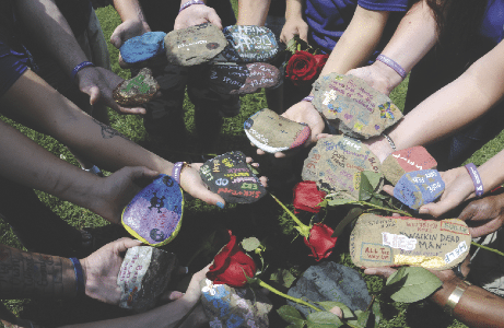Journal Photo by Ron Agnir Jefferson Day Report Center Program participants hold their personalized message recovery rocks one last time before letting the past go at the 2nd Annual Rock Burial Recovery Ceremony Thursday in Ranson.