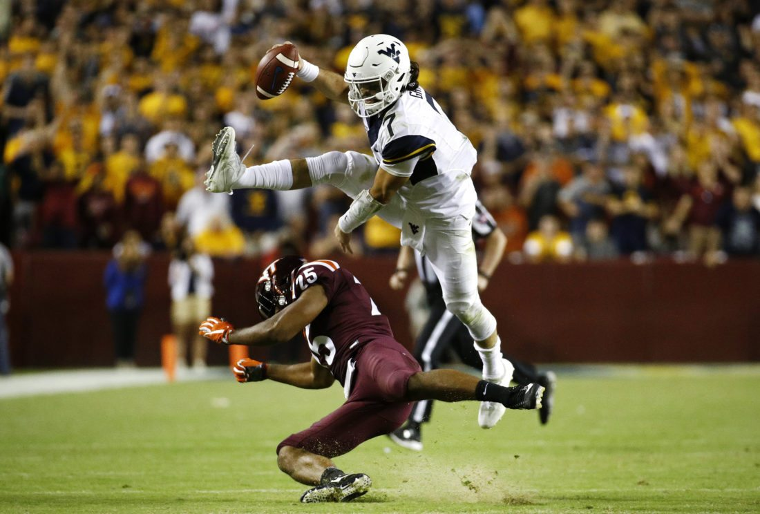 West Virginia quarterback Will Grier, top, leaps over Virginia Tech linebacker Anthony Shegog as he rushes for a first down in the second half of their game in Landover, Md., on Sunday.
