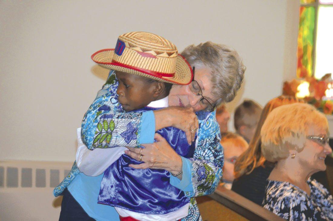 Journal photo by Adranisha Stephens Loria Webb, host of some of the Haiti Orphan Choir, gives a choir member a hug during prayer.
