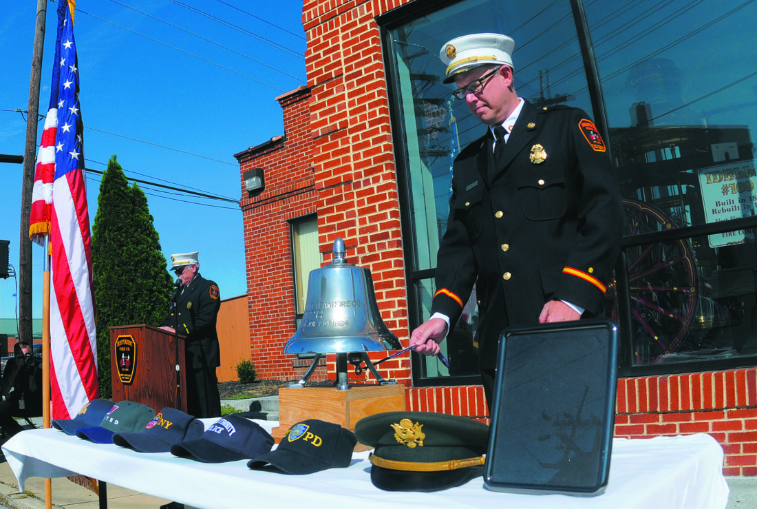 12 9-11 Remembrance1 ra 09-11-17 Jeff Plautz, Treasurer, Independent Fire Company, rings the fire bell as Henry Christie, Chaplain, relects on the people who lost their lives on board, American Airlines Flight 11 & Flight 77, United Airlines Flight 175,  FDNY, Port Authority Police, NYPD, and the Pentagon Tuesday morning at the Independent Fire Company 9/11 Remembrance in Ranson. The empty picture frame represents the lost memories from everybody's lives that were affected. (Journal Photo by Ron Agnir)
