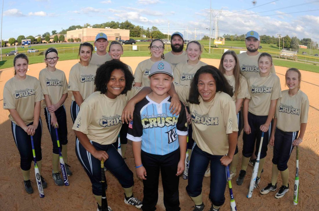 Journal photo by Ron Agnir Members of the Panhandle Crush 14U softball team stand with BraylonConner, middle, a member of the Crush's baseball team. The softball team will show support for Conner and Kailan Haught, a member of the 16U softball team, in this weekend's Going Gold for Childhood Cancer tournament. Conner and Haught both have suffered from leukemia.