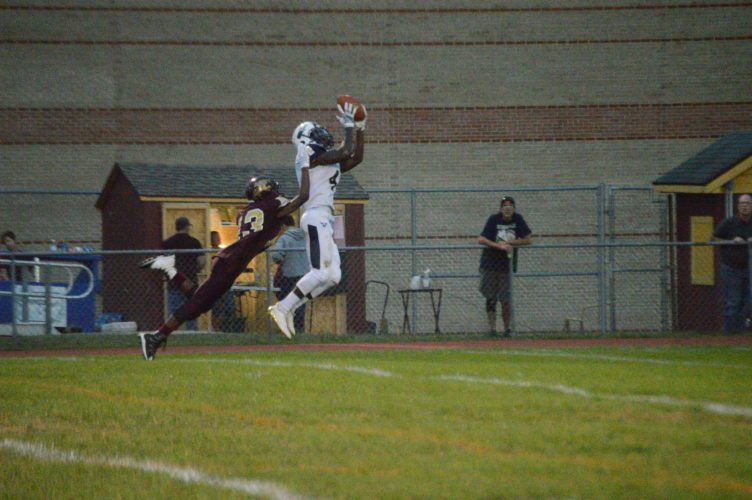 Hedgesville's Niyjere Smith, right, catches a pass as Jefferson's Jon Gidney defends during their game Friday night in Shenandoah Junction.