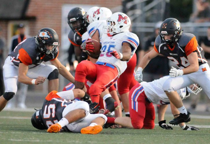 Journal photo by Ron Agnir Martinsburg defenders Ricky Barrett (46), Mikey Jackson (25) and Aaron Pierson (24) gang tackle Morgantown running back Javohn Moore, middle, during first-quarter action on Friday night at Cobourn Field. See more photos on CU.journal-news.net.