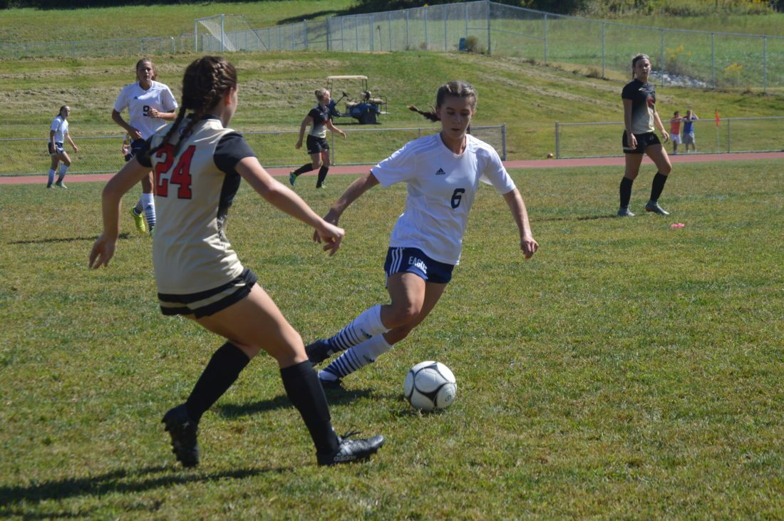 Journal photo by Jessica Manuel Hedgesville's Natalia Roppolo, right, works the ball around University's Madylin Hinkle during their game on Saturday in Hedgesville.