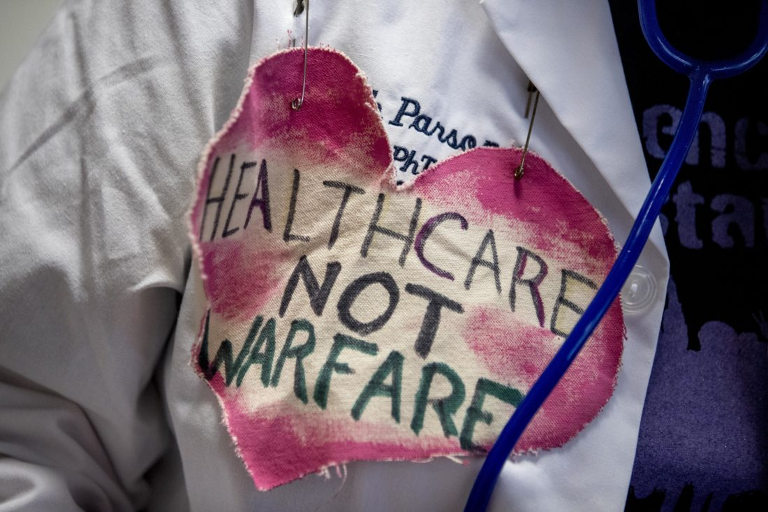 "Ann Wright of Honolulu, wears a heart that reads ""Healthcare Not Warfare"" on a doctors coat as she joins others outside a hearing room where the Senate Finance Committee will hold a hearing to consider the Graham-Cassidy healthcare proposal, on Capitol Hill , Monday, Sept. 25, 2017, in Washington. (AP Photo/Andrew Harnik)"