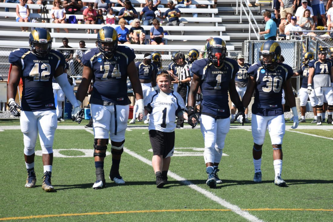 Jason Bednarski (center), of Team IMPACT, serving as honorary team captain for the Shepherd Rams football during the September 23 home game, walks with several Ram players to the center of the field to help with the coin toss. (Photo courtesy of Shepherd University)