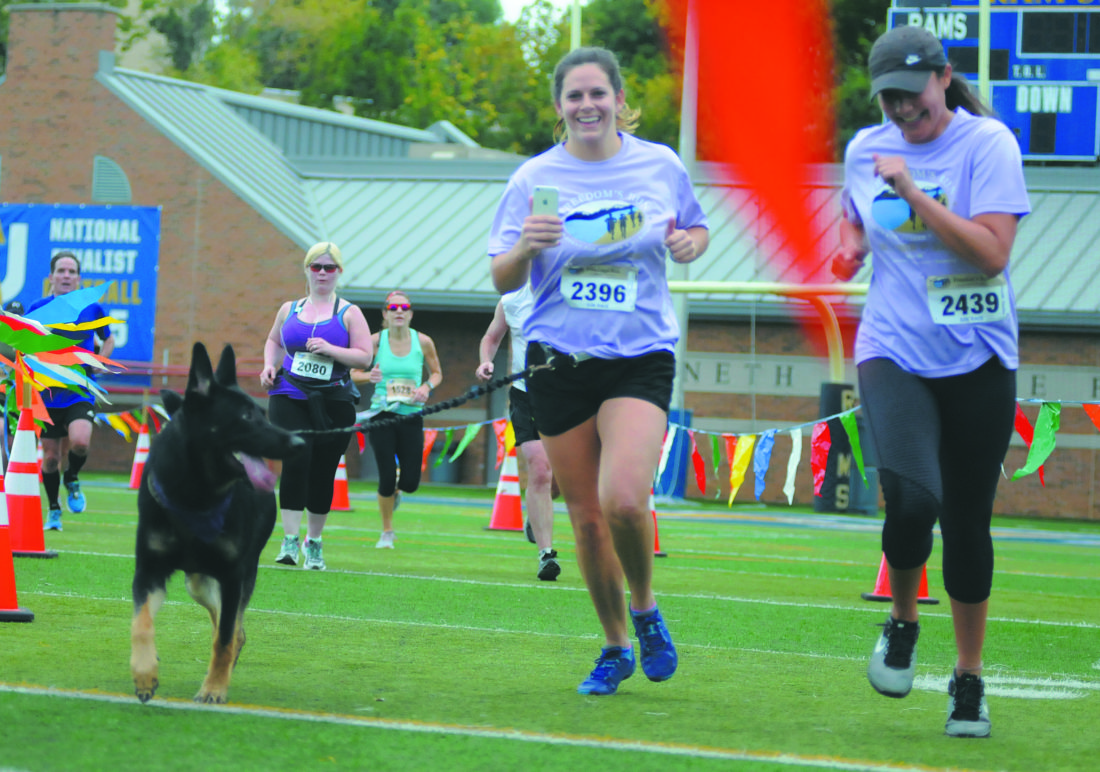 01 FR-10k Doggie ra 09-30-17 Shepherdstown residents Samantha Lemnah  (#2396) and Nicolette Hamilton cross the Freedoms Run 10K finish line with adoggie in a little over 01:29:00  Saturday morning in Shepherdstown. See more photos on CU.journal-news.net. (Journal Photo by Ron Agnir)
