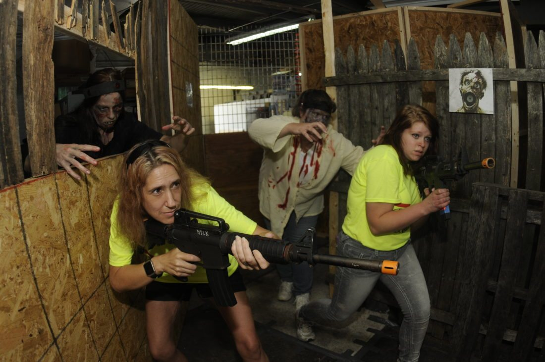 Jaimi Coomes and Abbie Woodard hunt for zombies Monica Turner and Lara Woodard. (Journal photo by Ron Agnir)