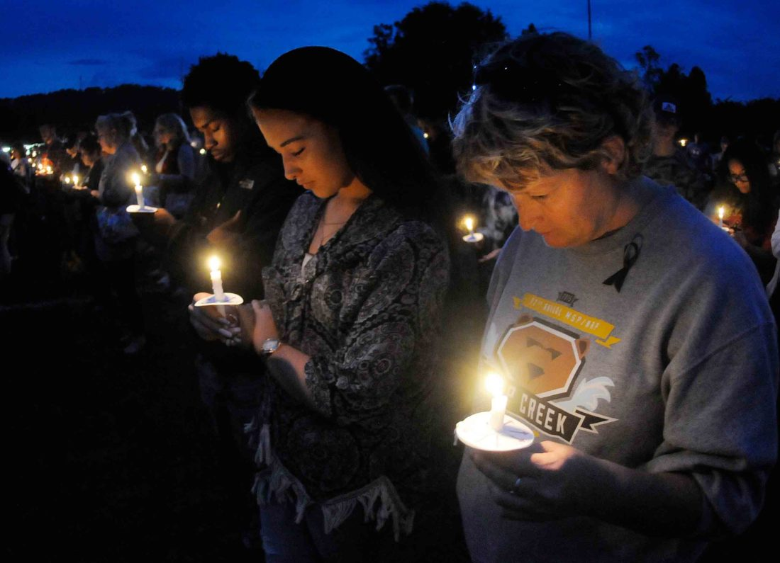 Djabril Burton, left, Alexis Hough and Brenda Hough bow their heads in a crowd of other mourners in a moment of prayer at the Denise Burditus candlelight vigil at Hedgesville High School Thursday evening.