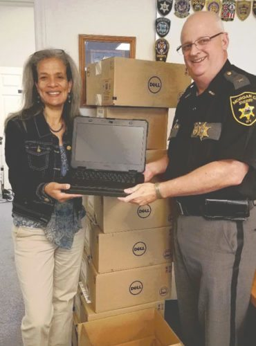 Margaret Walker, director, Eastern Panhandle Safe Community Program, presents Morgan County Sheriff K.C. Bohrer with a Dell computer as part of the Electronic Citation Program. (Submitted photo)