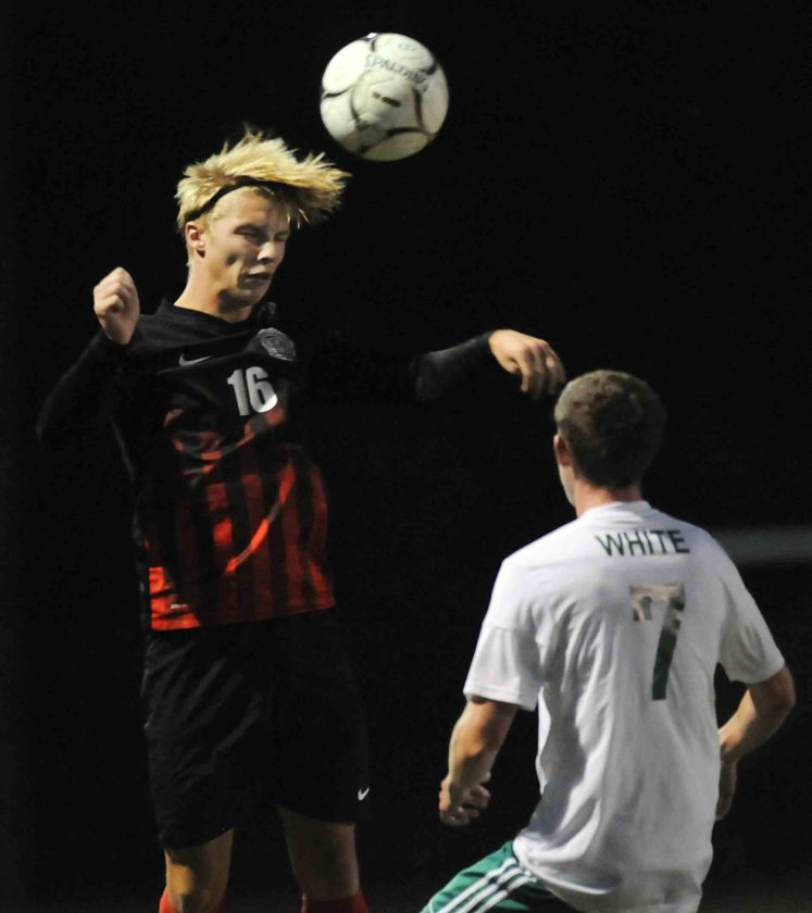 Journal photo by Ron Agnir Spring Mills' Josh Wiese, left, leaps to head the ball over Musselman's Andrew White during the first half of their match last week in Inwood. See more photos on CU.journal-news.net.
