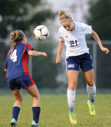Journal photo by Ron Agnir Hedgesville's Caroline Burton, right, heads the ball past Washington's Holly Goben during the first half of their game earlier this season. The Eagles and Patriots are the top seeds in their respective sectional soccer tournaments.