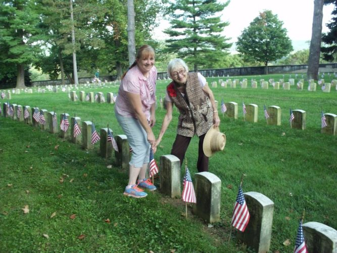 Regent Nancy Myers and Laura Shifflett (left) of the William Henshaw Chapter DAR, placed American flags at the grave stones of the Union dead from West Virginia on the 150th Anniversary of Antietam National Cemetery, Sept. 17. (Submitted photo)