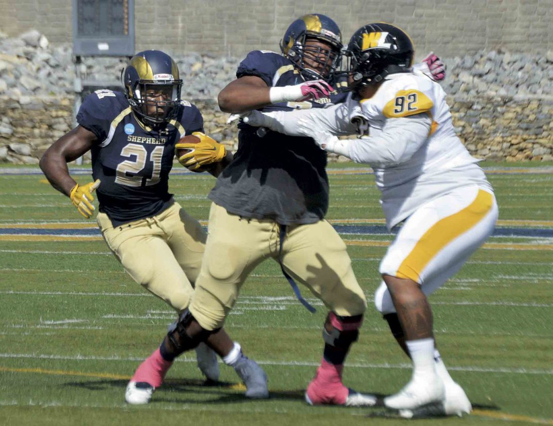Shepherd's Jabre Lolley, left, cuts for a big run against West Liberty during their game on Oct. 7 in Shepherdstown. (Journal photo by Jessica Manuel-Wilt)