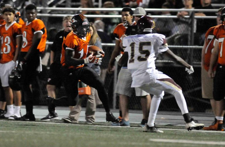 Martinsburg's Shy Crawford, left, jukes past Jefferson's Antione Lewis and races down the Bulldog sideline for the first touchdown of the game Friday night in Martinsburg. See more photos on CU.journal-news.net. (Journal photo by Ron Agnir)