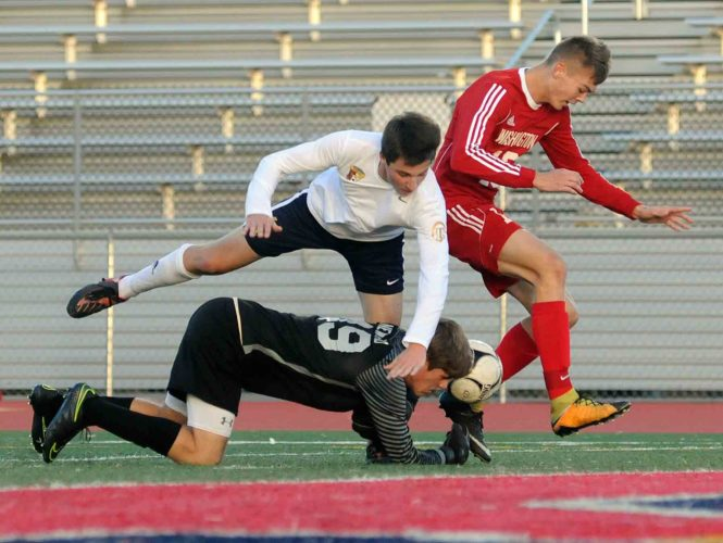 Hedgesville goalkeeper  Tommy Newland, bottom,  and  Austin Hougton, middle, collide as they shut down an attack by Washington's Michael Barr during first-half action Tuesday evening in the Class AAA, Region IIchampionship. See more photos on CU.journal-news.net.  (Journal photo by Ron Agnir)