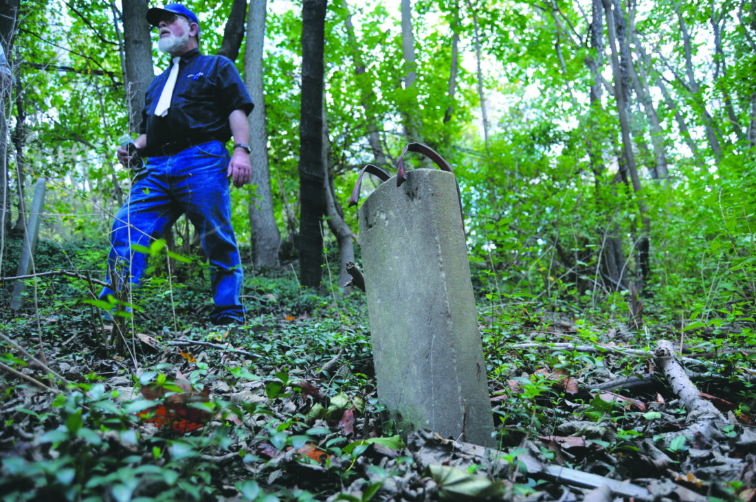 Peter Miller stands next to an unfinished gravestone on a hill side adjacent to Green Hill Cemetery and Tuscarora Creek where anywhere from 35 - 100 19th century graves sit mostly unmarked in the overgrown woods along Golf Course Road in Martinsburg Wednesday afternoon. He's hoping to find a committee to manage the approx. 1.5 acre of land. (Journal Photo by Ron Agnir)