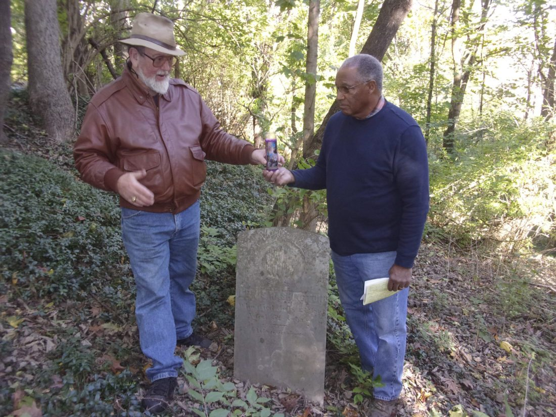Peter Miller, left, symbolically hands over care of the black cemetery at Green Hill Cemetery to the Rev. Ed Hall of Mt. Zion UM Church in Martinsburg, by passing a lighted candle as they stand next to a tombstone for Lewis Washington.