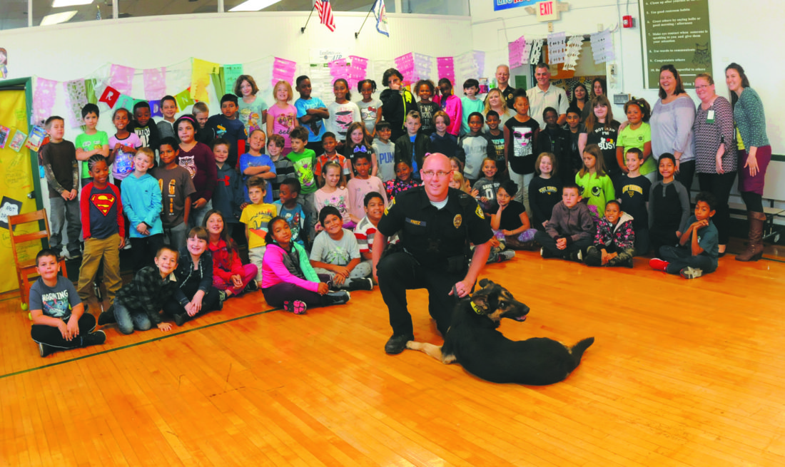 """18 MPD Canine3 ra 10-17-17 Martinsburg Police Canine Handler, Patrolman Ryan Fritz with """"Titan"""", the 14 mth old German Shepherd officer in front of 2nd & 3rd graders at Burke Street Elementary School Tuesday morning. Patrolman Fritz and Titan just completed an intensive six week training and certification course. Capable of reaching speeds of 30 mph and leaping over a 4 ft fence, Titan understands 8 commands (all in Dutch language) and will serve the community upwards of 8-12 year depending on health. (Journal Photo by Ron Agnir)"""