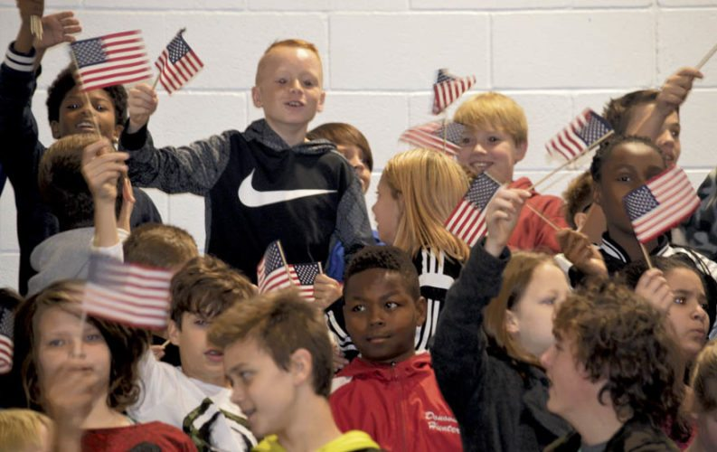 """Students at Spring Mills Middle School wave flags during the school's """"Veteran's Assembly.""""  (Journal  Photo by Nisha Stephens)"""
