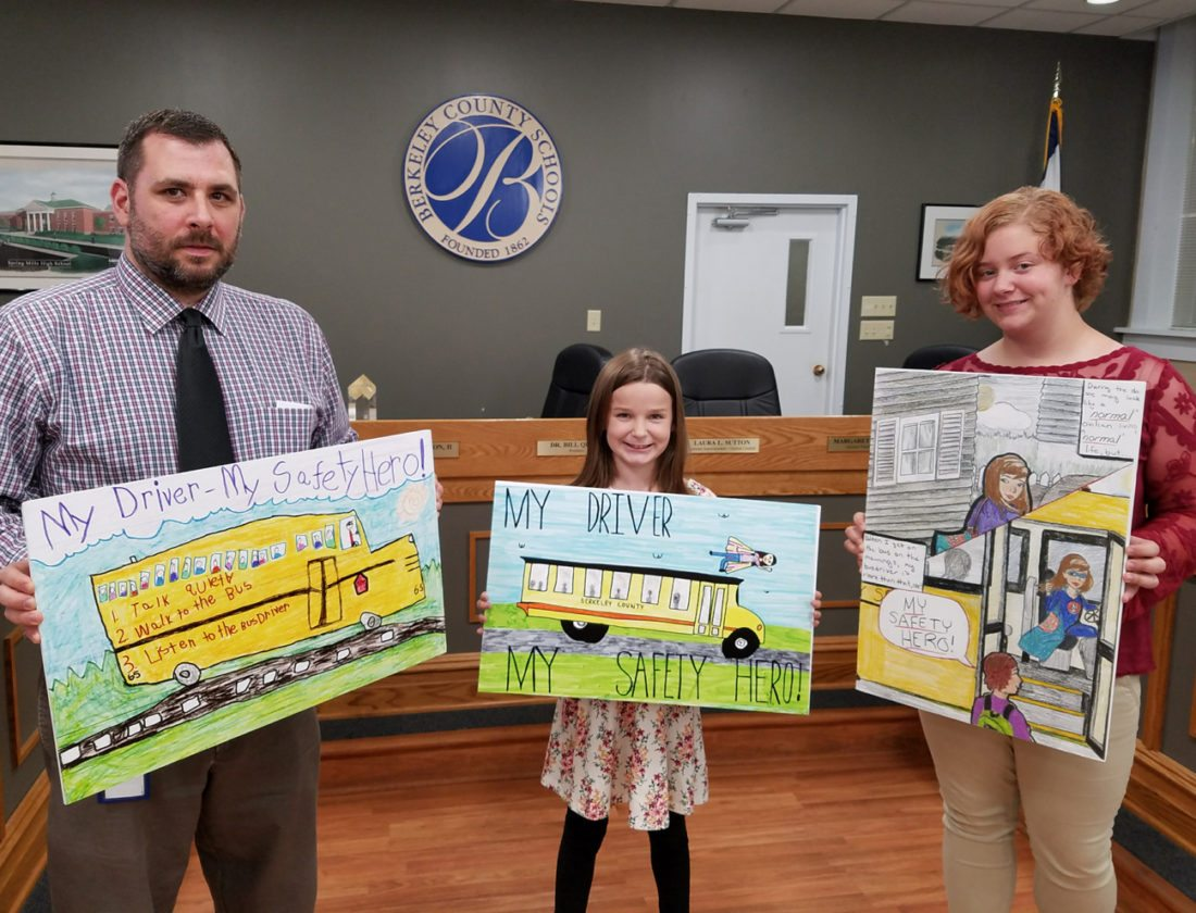 Pictured, from left, are JR Hollen, Executive Director of Transportation, holding the first place poster in the K-2 division created by Danica Simmons, first grader at Rosemont Elementary; Preslyn Heidel fourth grader of Eagle School Intermediate, third-fifth division; and Charity Lundberg, ninth grader from Mountain Ridge Middle School, recipient of first place sixth-eighth grade division. (Submitted photo)