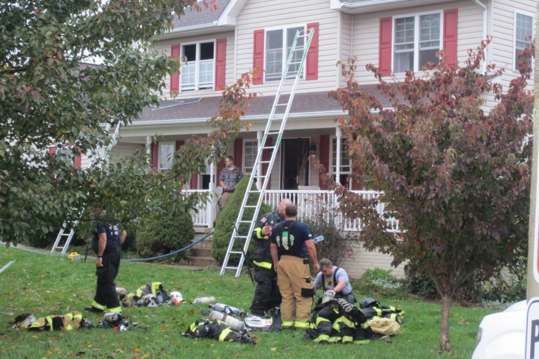 Firefighters dispatched to the Qail Run subdivision after having doused the house fire. (Journal photo by Tim Cook)