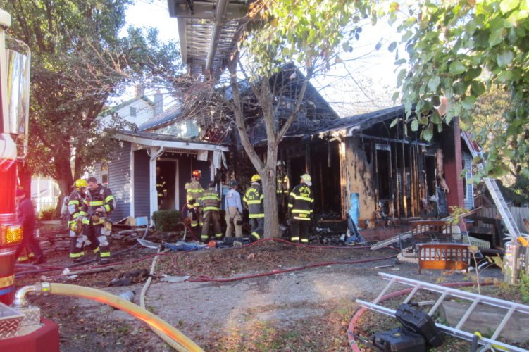 Journal photo by Tim Cook Crews work at the scene of a house fire on Friday, near Reedson.