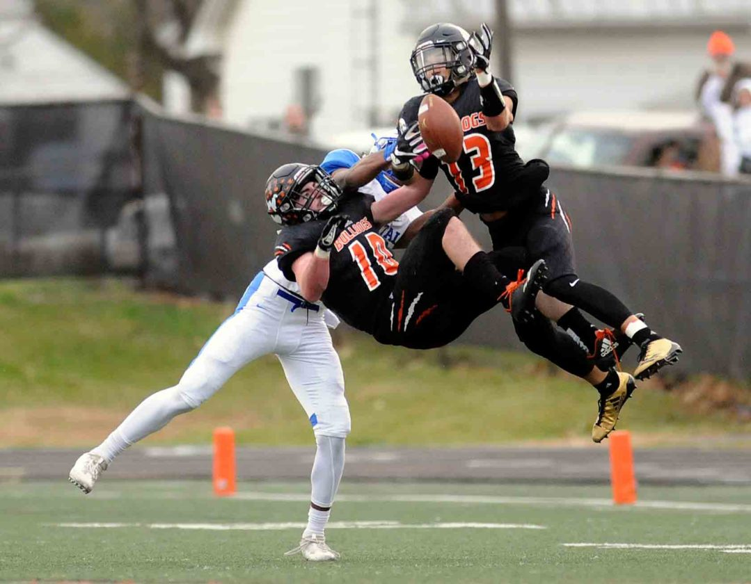 Martinsburg defensive backs Grant Harman (10) and Teddy Marshall collide as they knock a deep pass away from Capital wide receiver Anthony Pittman during Saturday's Class AAA semfinal game between Capital and Martinsburg.  (Journal photo by Ron Agnir)