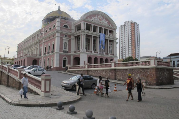 Tourists walk in front of the Teatro Amazonas in Manaus, Brazil. The theater was built during the rubber room in the 19th century. Today offers several shows a year and is one of the main tourist points for people visiting the Amazon rain forest around Manaus. (AP Photo/Peter Prengaman)