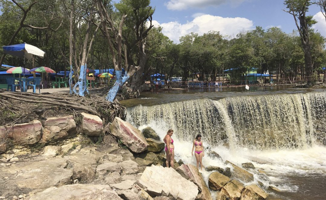 Amazon dwellers and tourists enjoy a waterfall on a tributary of the Rio Negro outside of Manaus. Many people live along the hundreds of large tributaries that feed into the main rivers in the Amazon basin. (AP Photo/Peter Prengaman)