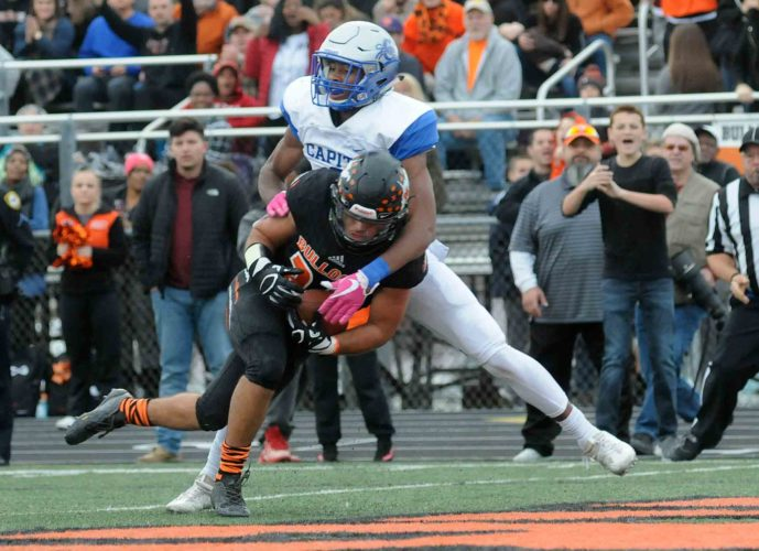 Journal photo by Ron Agnir Martinsburg's Mikey Jackson, front, barrels through Capital's Anthony Pittman for a touchdown during the fourth quarter of their Class AAA state semifinal game on Nov. 25 in Martinsburg.