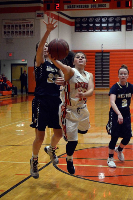 Journal photo by Jessica Manuel-Wilt Martinsburg's Deaira Hairston puts up a shot while being defended by James Wood's Makayla Firebaugh during their game on Tuesday in Martinsburg.