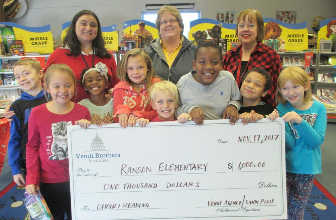 Third grade students at Ranson Elementary School pose with parent involvement coordinator, Monica Addison, office manager for Vendt Brother Agency with Allstate Insurance Company, Sandi Poole, and Ranson Elementary Librarian, Dr. Ann Mathena after receiving the Allstate Foundation Helping Hands in the Community Grant for choir and reading programs (Submitted photo)