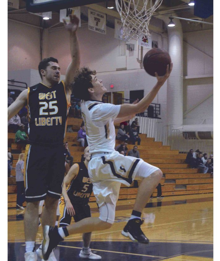 Cam Stephens of Shepherd goes up for a reverse layup against Evan French of West Liberty during the Hilltoppers' victory on Wednesday. (Journal photo by Jessica Manuel-Wilt)