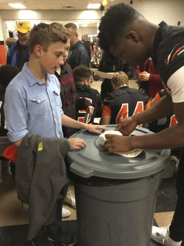 Martinsburg's Tavis Lee signs an autograph for Gavin Stenger during the Bulldogs' celebration for winning the Class AAA state title on Thursday. (Journal photo by Rick Kozlowski