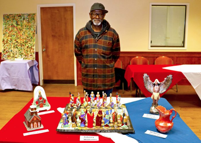Johnny Williams stands in front of his chess pieces he created. (Submitted photo)