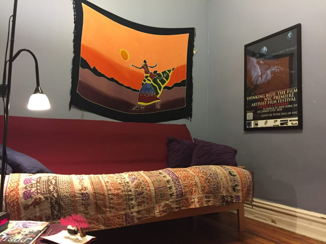 """A bedroom in a New York City apartment being used as a """"woman cave,"""" with a scarf hung on the wall, futon with throw pillows, a good reading lamp, small works of art and keepsakes from loved ones and other decorative touches. (AP photo)"""