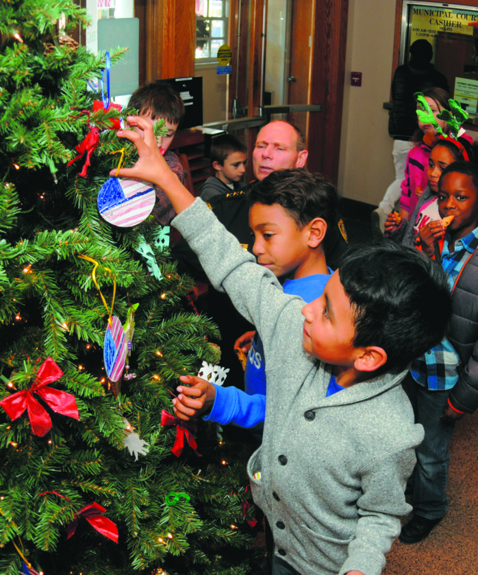 21 City Hall Xmas tree1 ra 12-20-17 Martinsburg Police Chief Maury Richards helps Burke Street Elementary School 3rd graders Eli Wheeler, Maurilio Chayarro, Jesus Gutierrez decorate a Chiristmas Tree in City Hall Wednesday afternoon. (Journal Phtoo by Ron Agnir)