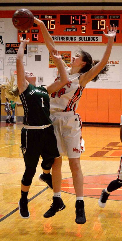 Journal photo by Jessica Manuel-Wilt Martinsburg's Morganne Andrews blocks the shot of Hampshire's Hannah Gordon during the second quarter of the Bulldogs' victory over the previously undefeated Trojans. (Journal photo by Jessica Manuel)