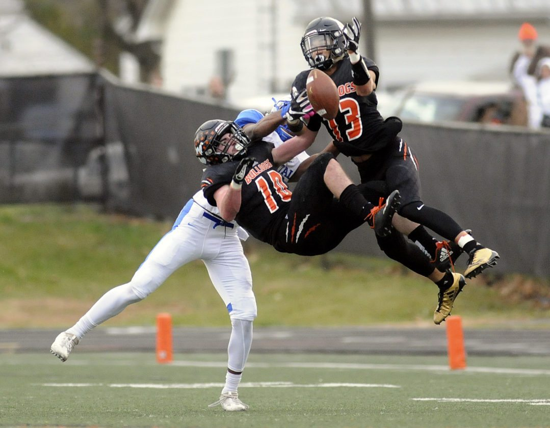 Martinsburg's Grant Harman (10) and Teddy Marshall (13) collide as they knock a deep pass away from Capital's Anthony Pittman during their Class AAA state semifinal game. Bulldogs defeated the Cougars 49-28.