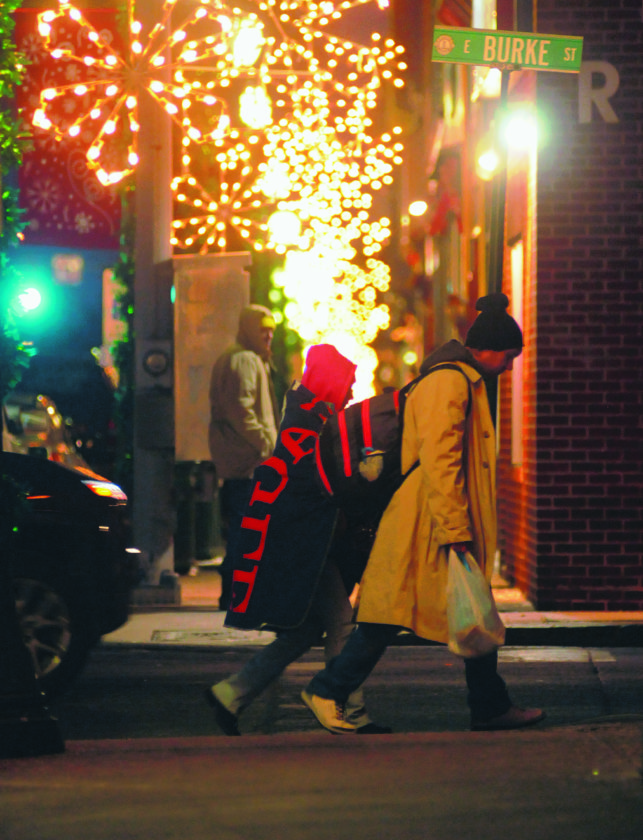 03 Cold Weather ra 01-02-18 Pedestrians use coats, hats and even blankets to stay warm as they walk along Bure Street in downtown Martinsburg as temperatures plunge below freezing Tuesday evening. (Journal Photo by Ron Agnir)