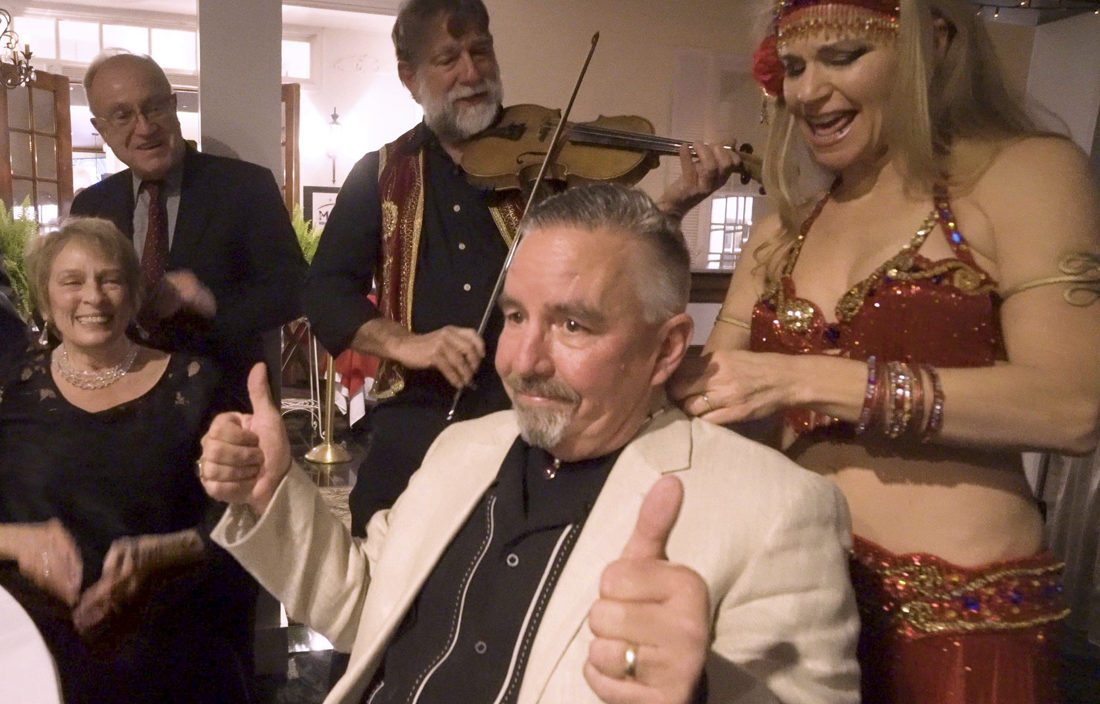 """Dave Smith gives a """"thumbs up"""" on winning the bid — three times — for a handcrafted ruby necklace at the Morgan Arts Council's annual Art and Elegance fundraiser.  Also in the photo from left are Karen Brown, chair of the event; Peter Brown; Mike Kligerman; and Jennifer Carpenter Peak, Jensuya Belly Dance. (Journal photo by Jeanne Mozier)"""