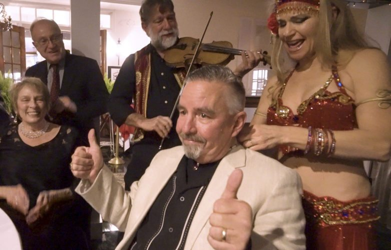 "Dave Smith gives a ""thumbs up"" on winning the bid — three times — for a handcrafted ruby necklace at the Morgan Arts Council's annual Art and Elegance fundraiser.  Also in the photo from left are Karen Brown, chair of the event; Peter Brown; Mike Kligerman; and Jennifer Carpenter Peak, Jensuya Belly Dance. (Journal photo by Jeanne Mozier)"